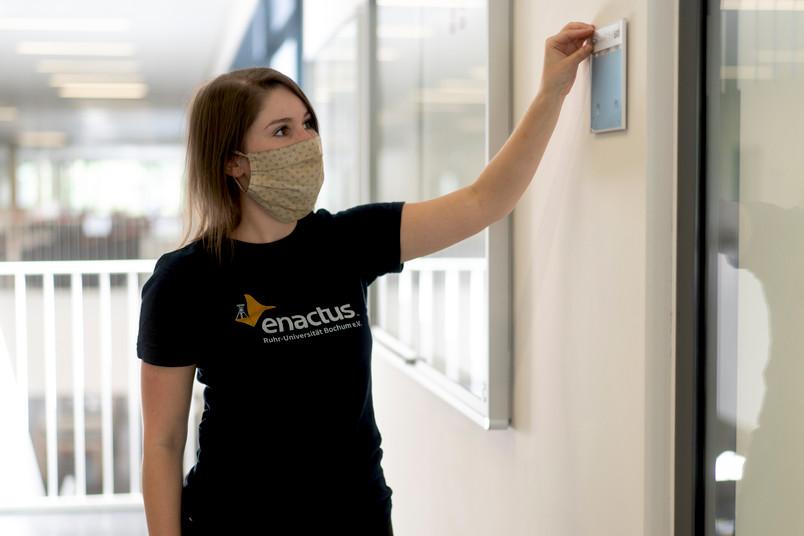 Eine junge Frau mit enactus RUB T-Shirt, die eine Braille Beschriftung an einem Raum der RUB anbringt.