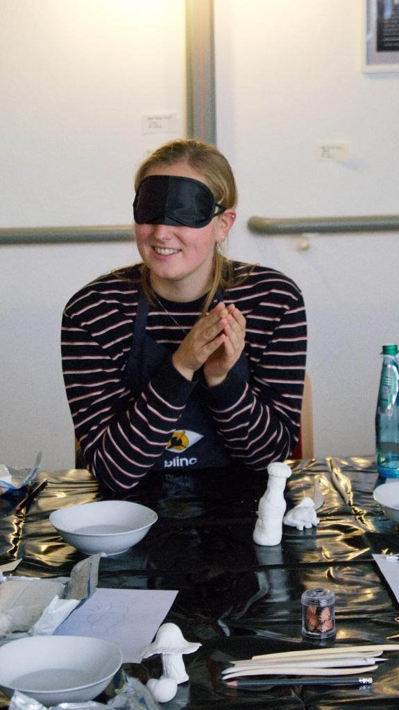 Eine Teilnehmerin befühlt ihren Ton mit verbundenen Augen. Um sie herum sind einige Materialien zu sehen. Außerdem einige fertige Tonkunstwerke: Eine kleine Flasche und ein Pilz.