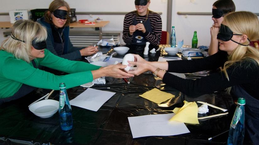 Mehrere Workshopteilnehmer sitzen mit verbundenen Augen am Tisch. Zwei von ihnen reichen sich über den Tisch hinweg einen Klumpen Ton. Die anderen Teilnehmer im Hintergrund formen ihre Figuren.