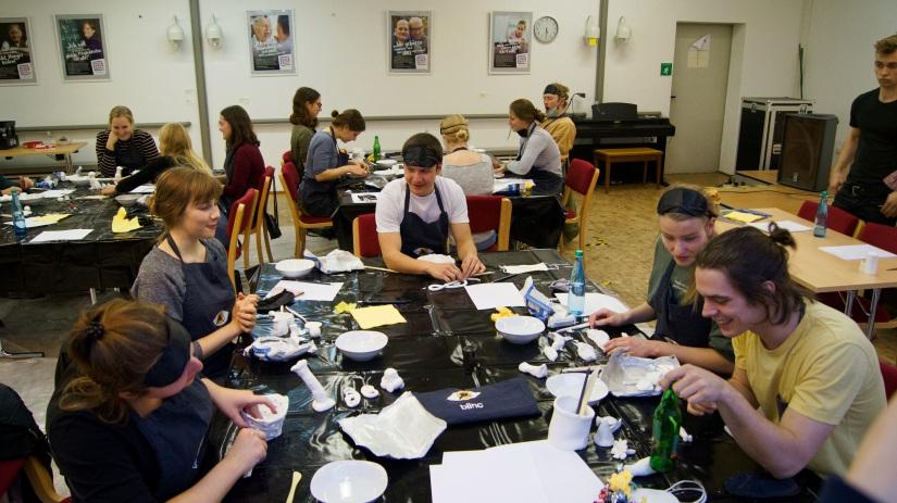 Zu sehen sind mehrere Tische mit  je 4 bis 5 Workshopteilnehmern. Diese machen sich mit dem Tonmaterial vertraut, zunächst noch ohne Augenmasken.