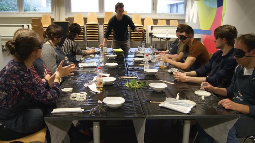 Unser Workshopleiter Samuel, der gerade einen Kunstworkshop leitet. Er steht am vorderen Ende des Tisches. An den Tischen sitzen 8 Personen, mit Augenmaske und Ton in der Hand.