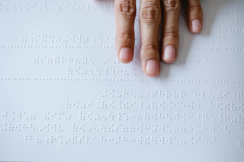 Eine Hand, die gerade Braille liest.
