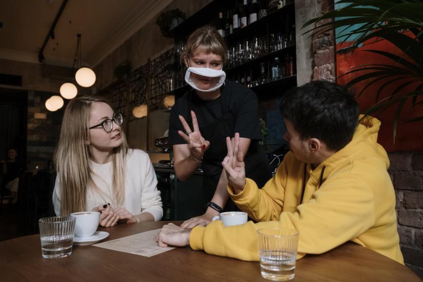 Zwei Personen, die am Tisch sitzen und mit einer Kellnerin gebärden. Die Kellnerin hat einen Mundschutz mit Sichtfenster auf.