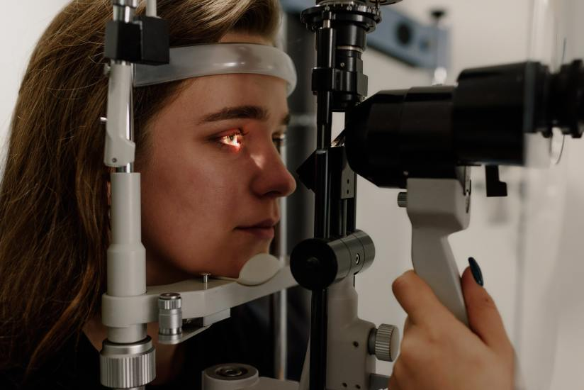 Eine junge Frau, deren Kopf in einem Gerät zur Messung der Sehschärfe liegt.