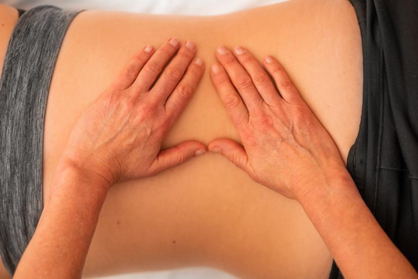 Zwei Hände, die den Rücken einer Person betasten, welche in Sportkleidung auf einem Tisch liegt.