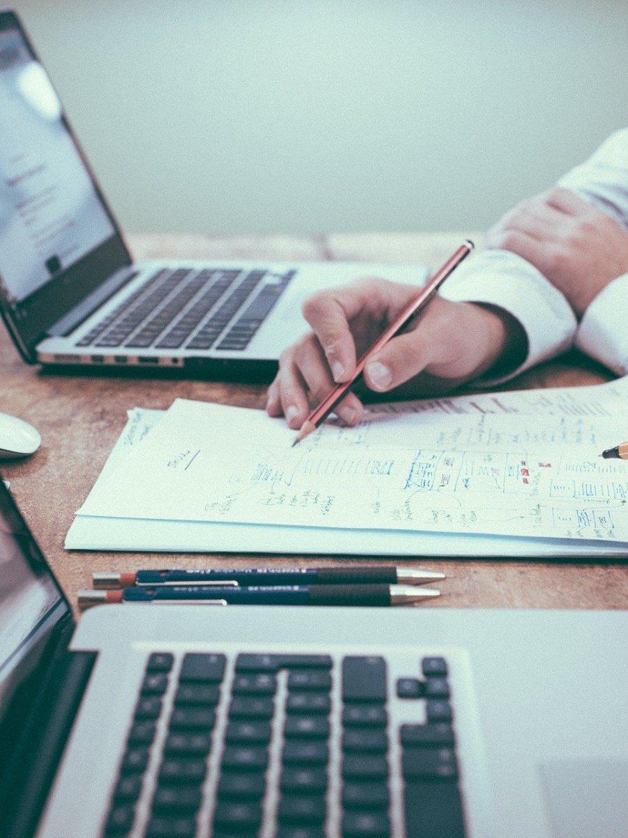 Zwei Studierende, mit offenen Laptops am Tisch. Machen sich Notizen auf Papier.