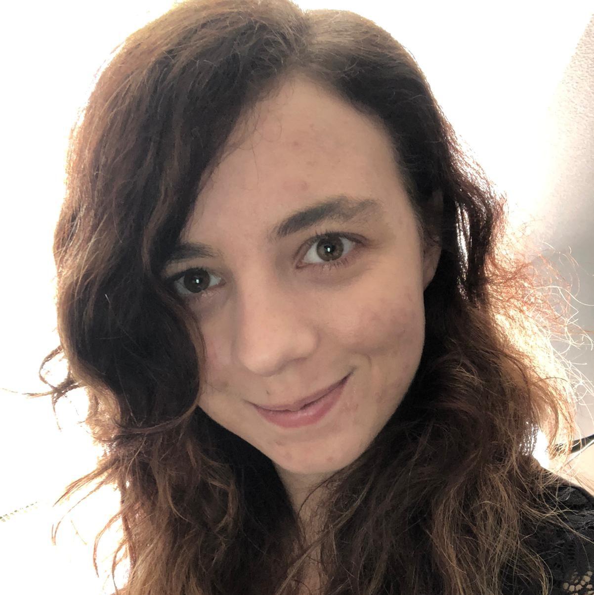Hier siehst du unsere Workshopleiterin Nadine. Sie hat dunkelbraune Haare und braungrüne Augen und lächelt in die Kamera.