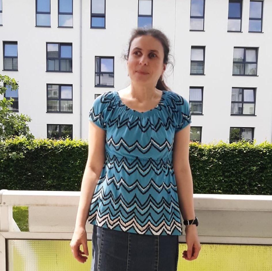Hier siehst du unsere Workshopleiterin Resi. Sie hat braune Haare und braune Augen. Hier trägt sie ein gemustertes blaues Oberteil und einen Jeansrock.